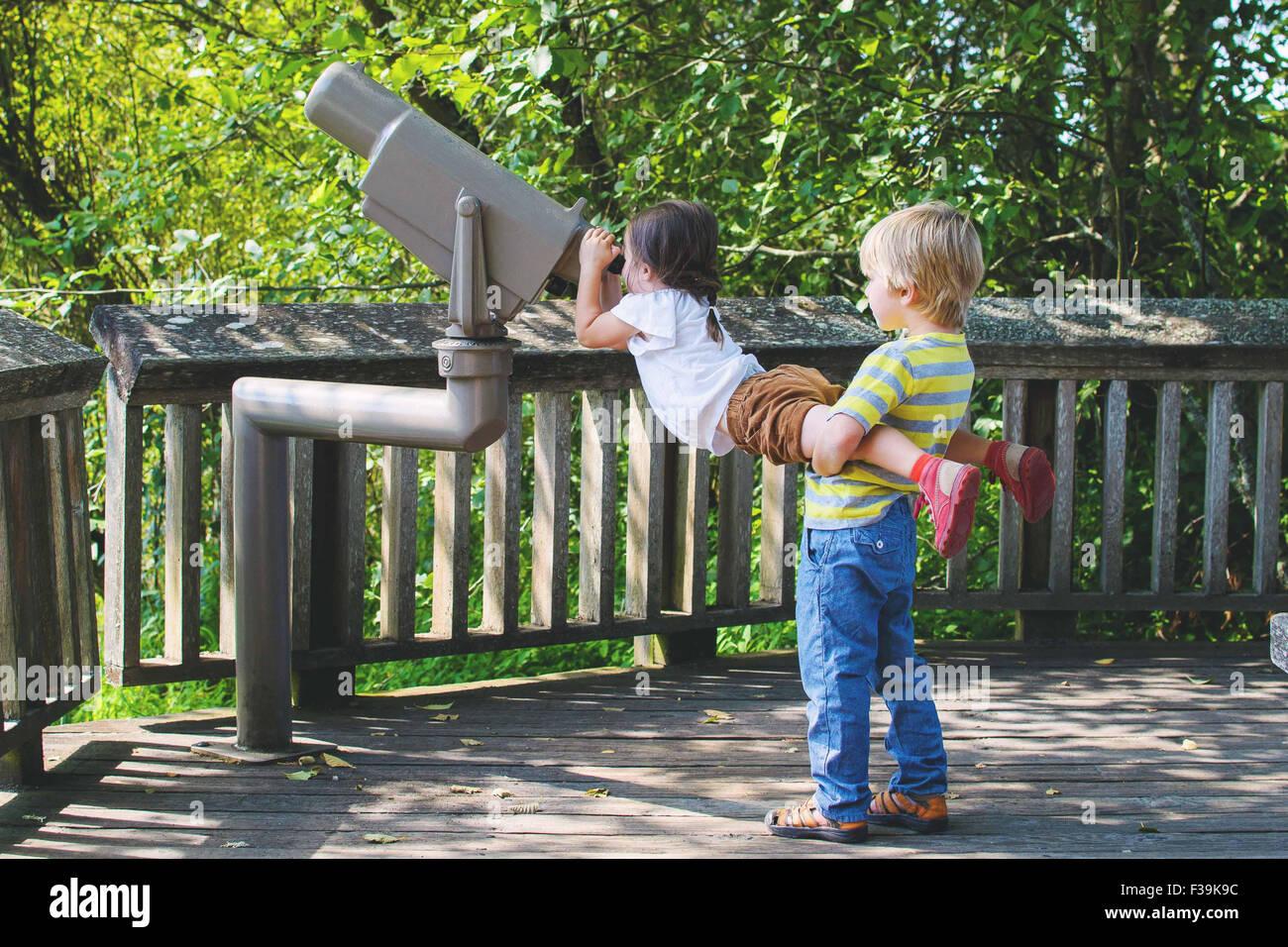 Ragazzo ragazza di sollevamento di guardare attraverso il telescopio Immagini Stock