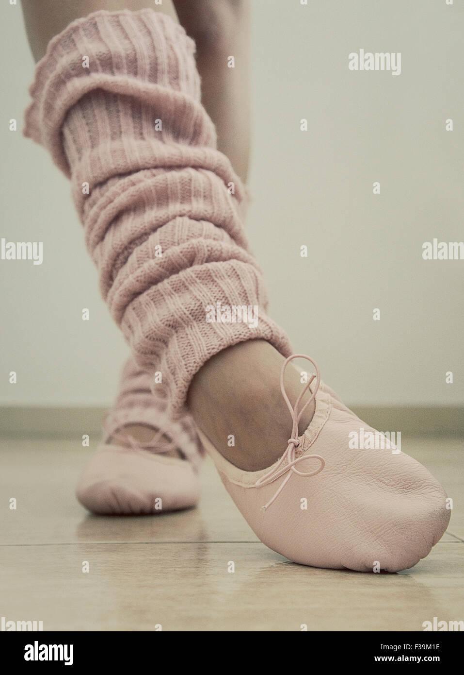 Close-up di una ragazza adolescente per le gambe, scarpe da ballo e gamba scaldabiberon Immagini Stock