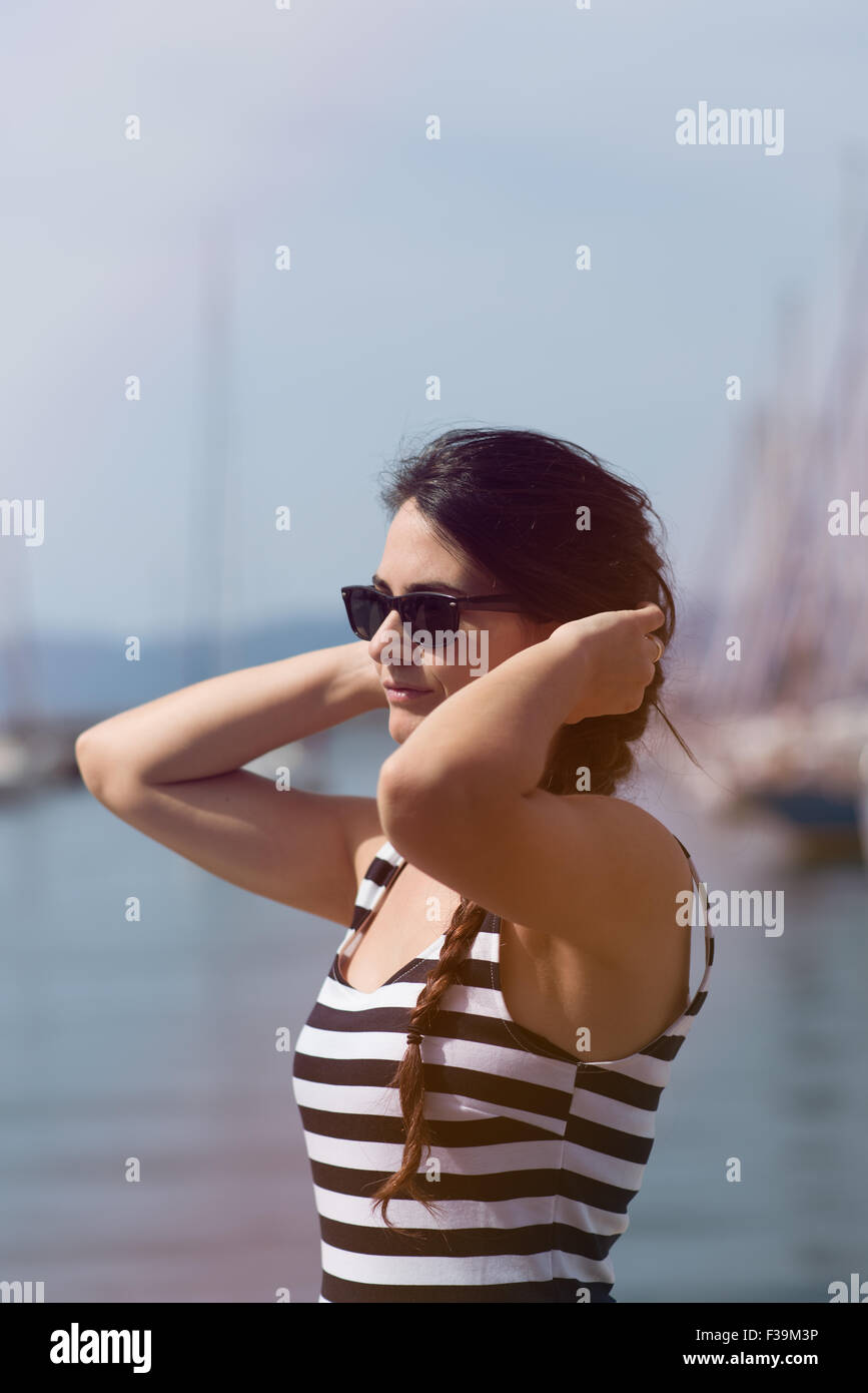 Ritratto di una giovane donna tenendo le sue mani per le sue orecchie Immagini Stock