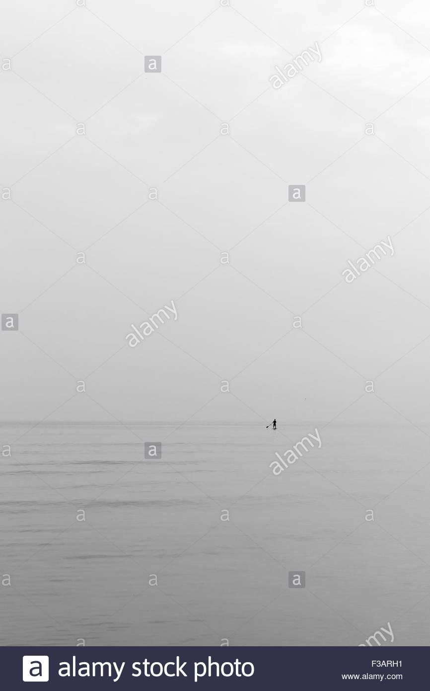Gli uomini sulla paletta da soli in mare Immagini Stock