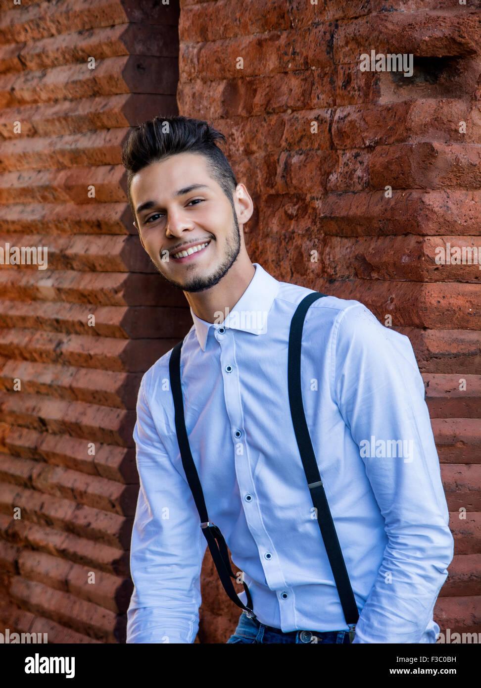 Attraente giovane uomo seduto contro un muro di mattoni, guardando la telecamera sorridendo. Tre quarti shot Immagini Stock