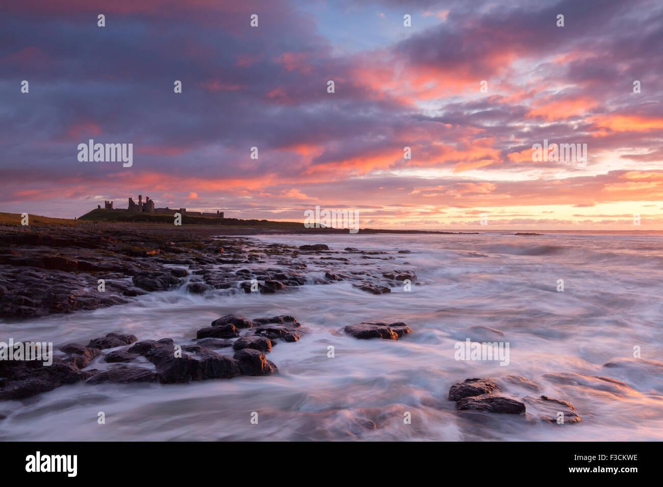 Il castello di Dunstanburgh sunrise, onde che si infrangono sulla spiaggia rocciosa appena lungo da Craster, Northumberland, Foto Stock