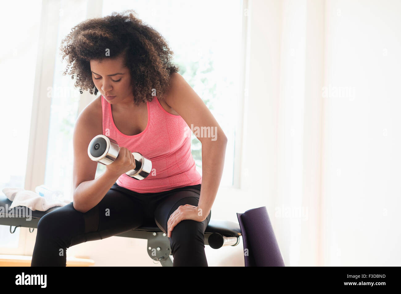Giovane donna allenamento con i pesi Immagini Stock