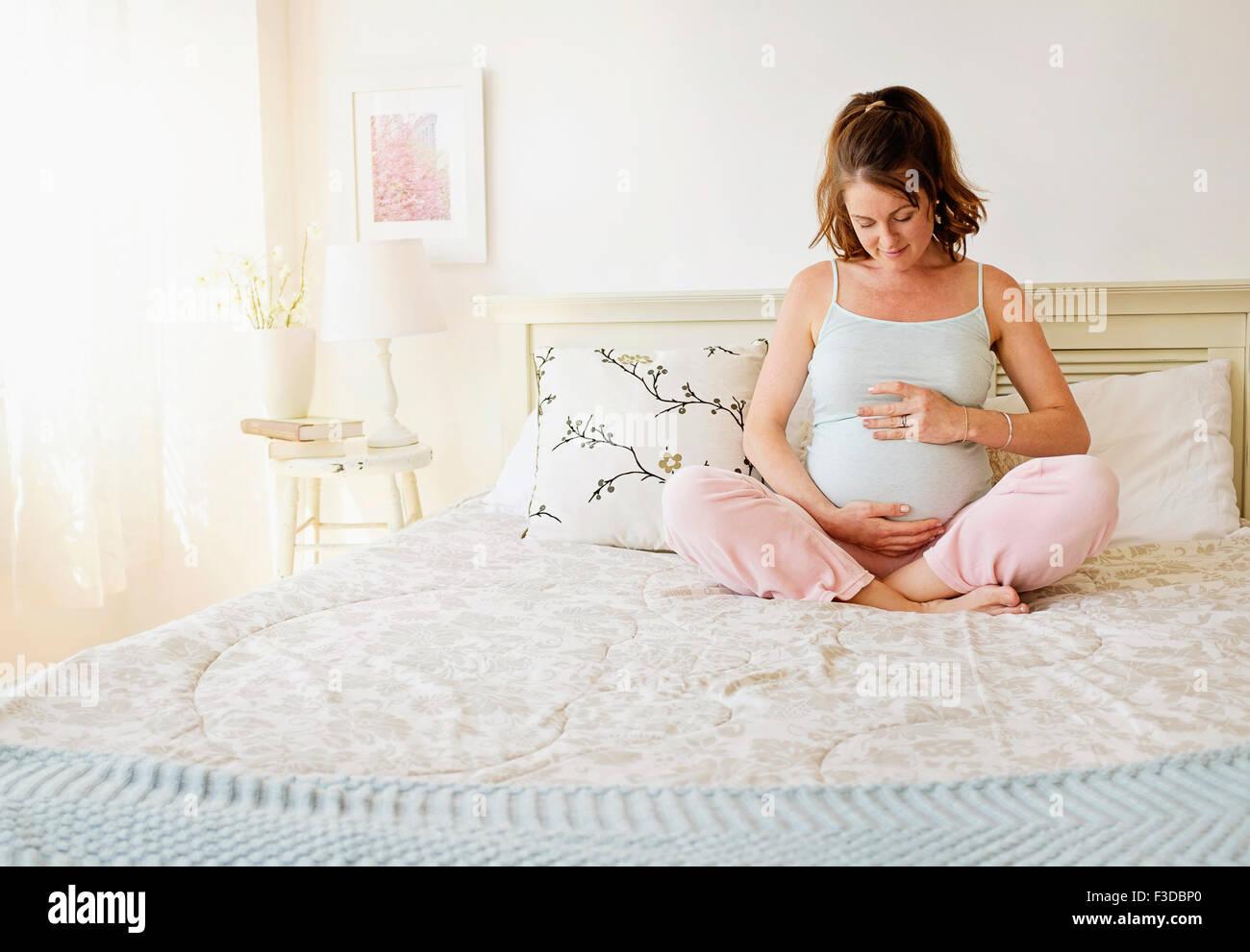Sorridente donna incinta seduta sul letto Immagini Stock