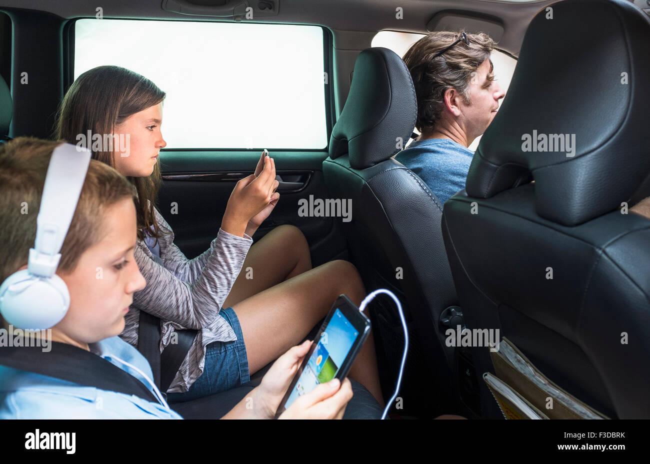 Bambini (8-9, 10-11) texting nel sedile posteriore Immagini Stock