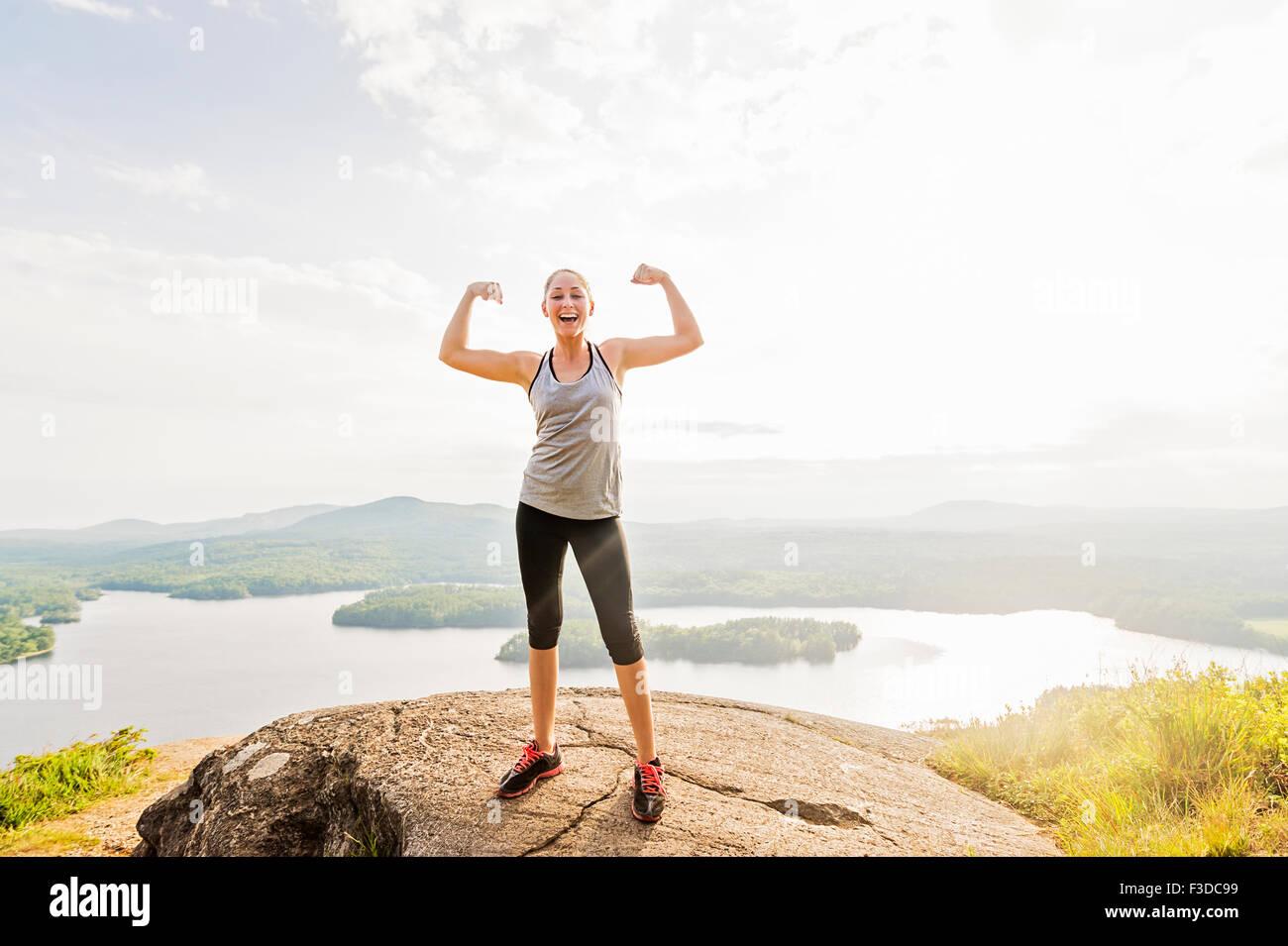 Giovane donna in piedi sulla cima della montagna e la flessione di muscoli Immagini Stock
