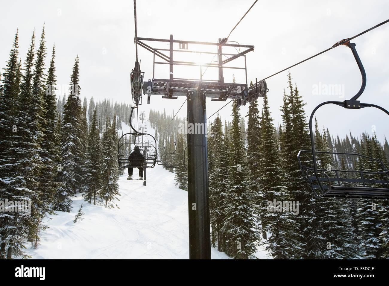 Uomo in ski lift, vista posteriore Immagini Stock