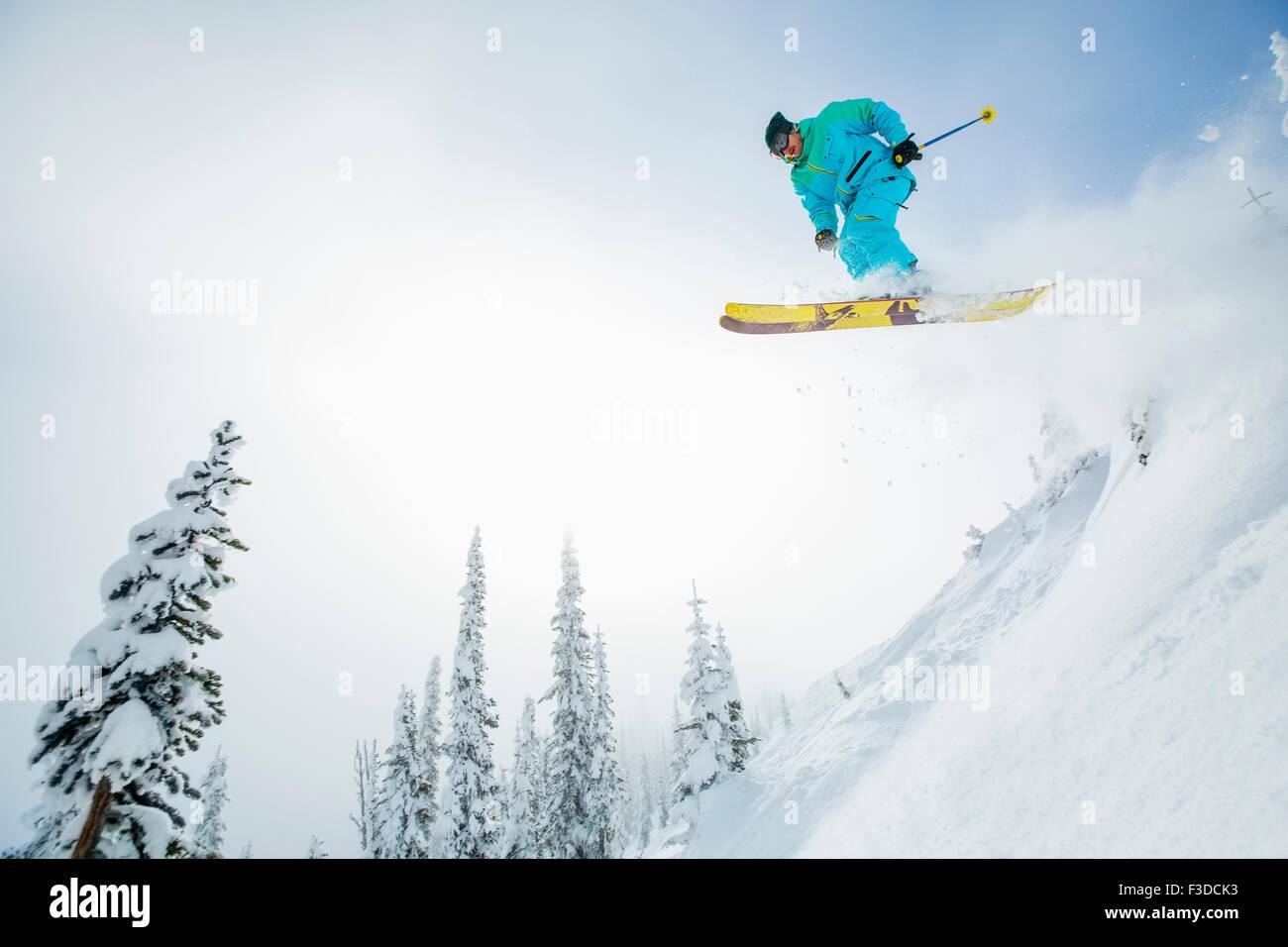 Giovane uomo saltando dalla pista da sci Immagini Stock