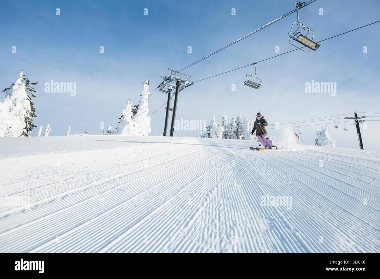 Metà donna adulta sulla pista da sci sotto il cavo auto Immagini Stock