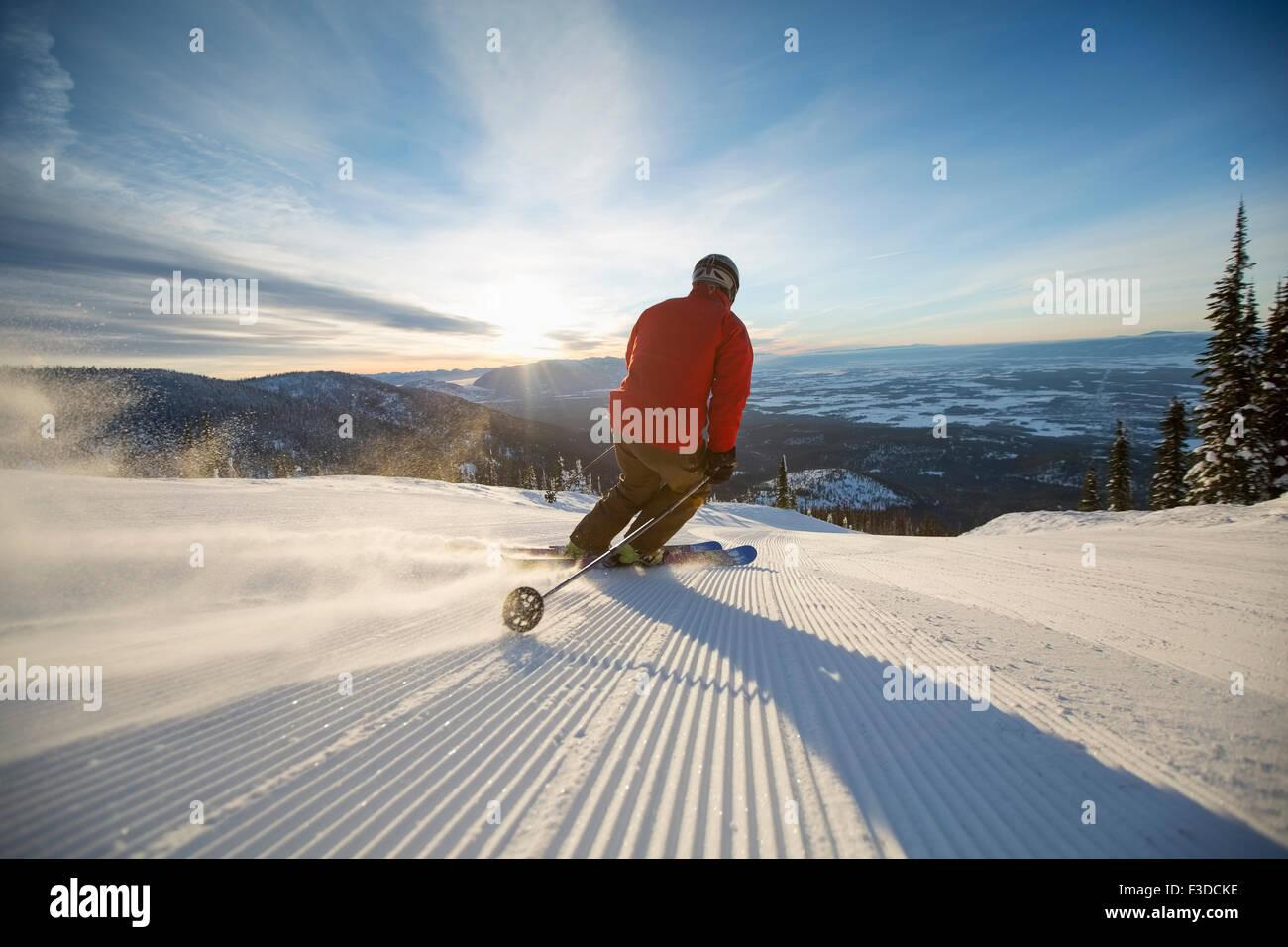 Uomo maturo sulla pista da sci al tramonto Immagini Stock