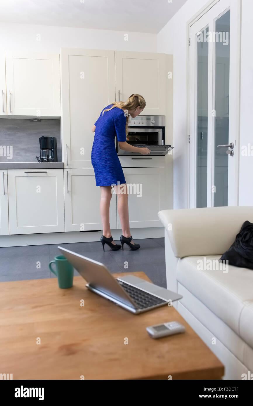 Donna in vestito blu cottura a casa Immagini Stock
