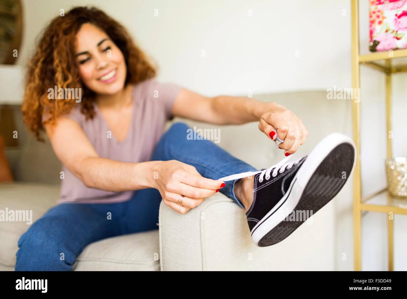 Donna mettendo sul trainer Immagini Stock