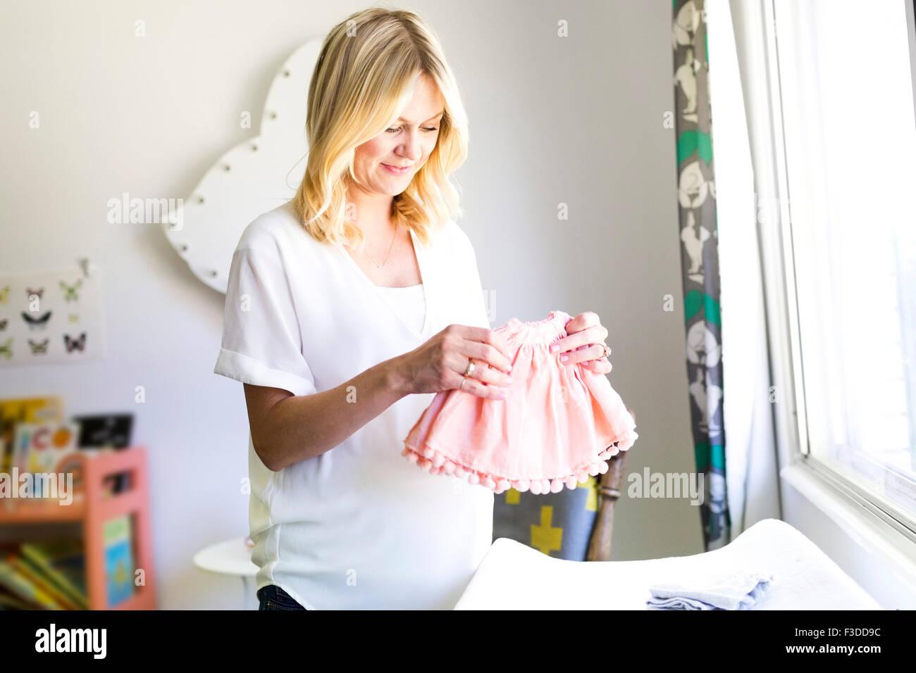 Donna incinta azienda abbigliamento bambino Foto Stock