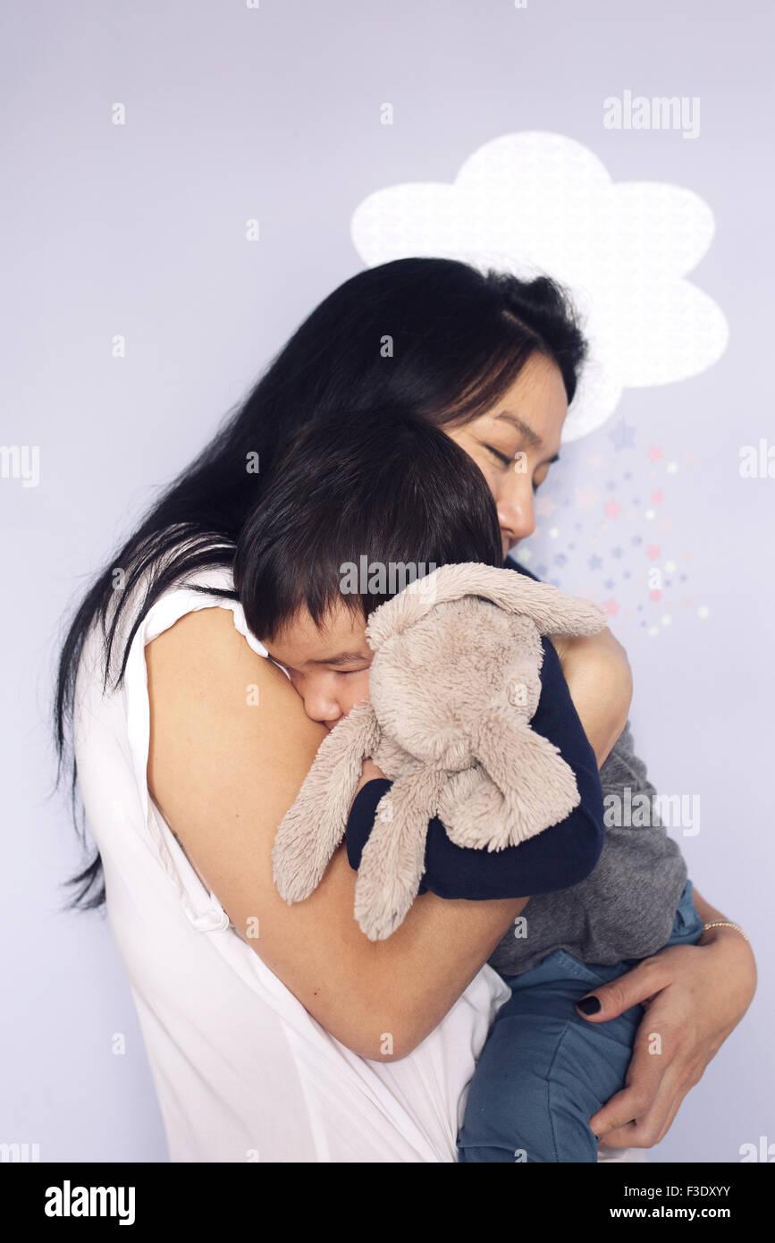 Madre abbracciando giovane figlio Immagini Stock