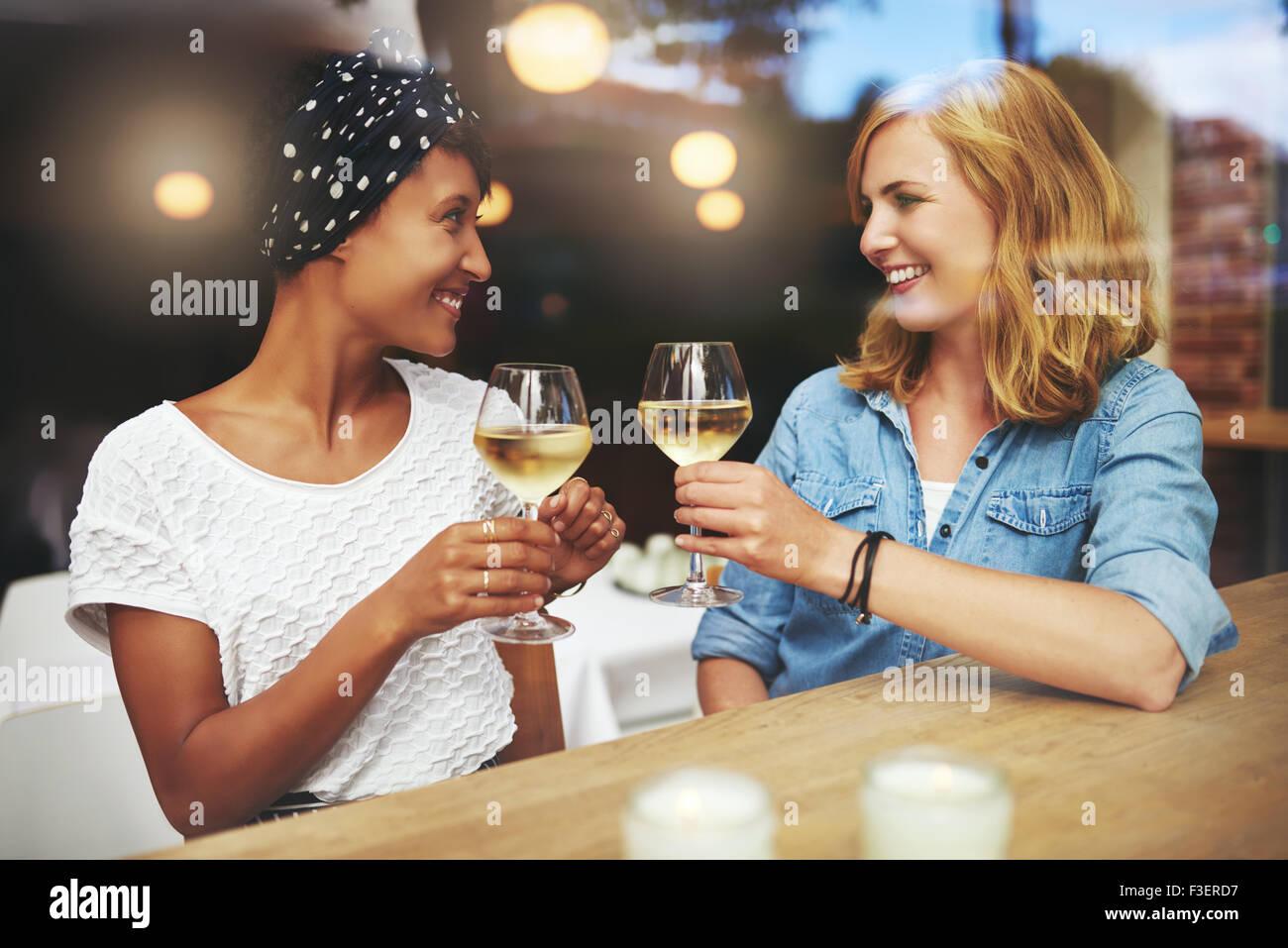 Piuttosto giovani donne la tostatura a vicenda con i bicchieri di vino bianco come si incontrano in un pub per una Immagini Stock