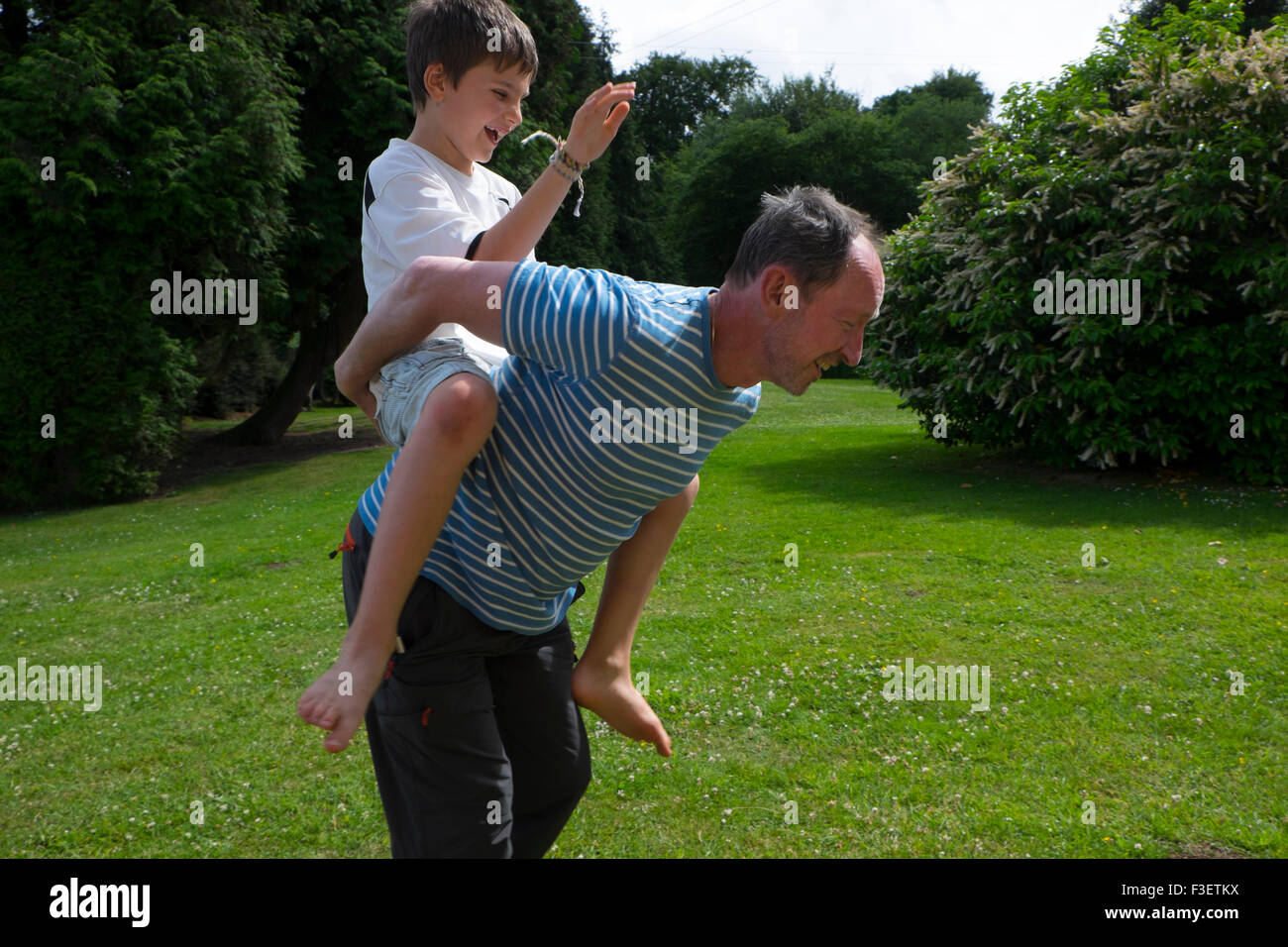 Uomo di 50 anni giocando con 8 anno vecchio nipote nel giardino, Monmouth, Powys, England, Regno Unito Immagini Stock