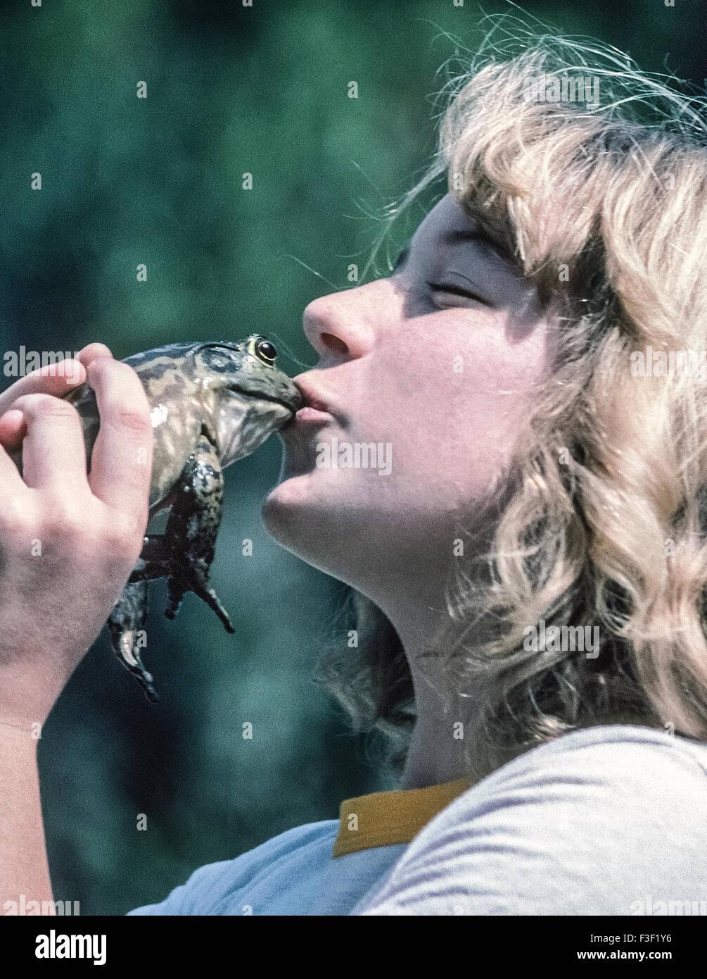 Una giovane ragazza bacia il ranocchio durante una rana jumping contest in Del Mar, California, Stati Uniti d'America. Immagini Stock