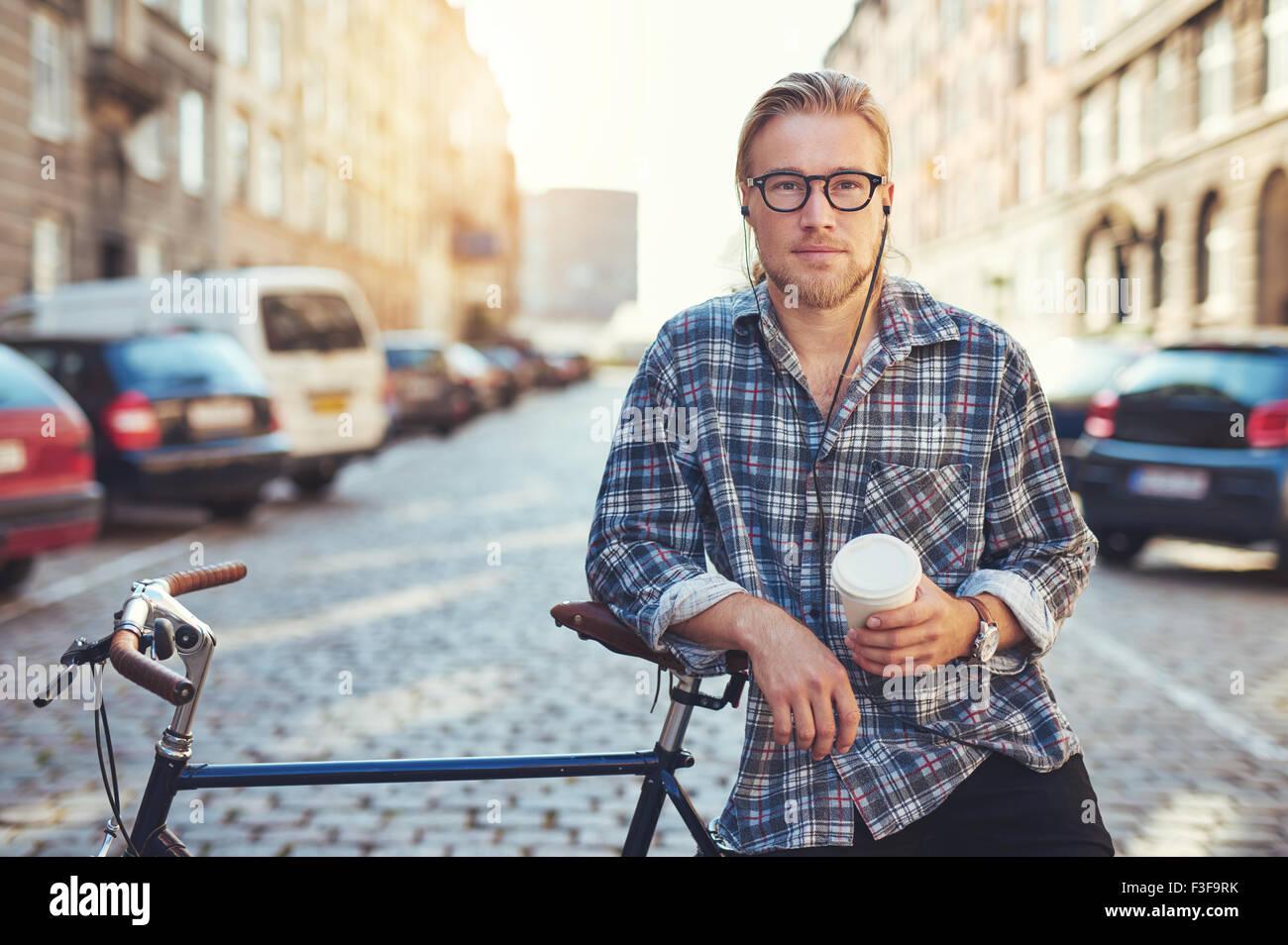 Raffreddare un uomo guarda la fotocamera. Lo stile di vita della città per godersi la vita in città Immagini Stock