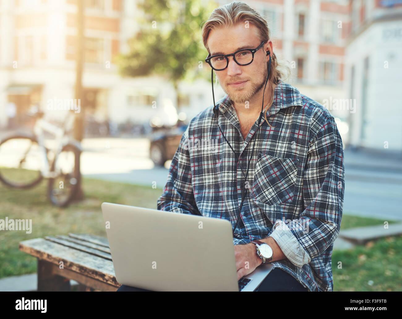 Imprenditore con computer portatile al di fuori seduta di lavoro. Lo stile di vita della città Immagini Stock