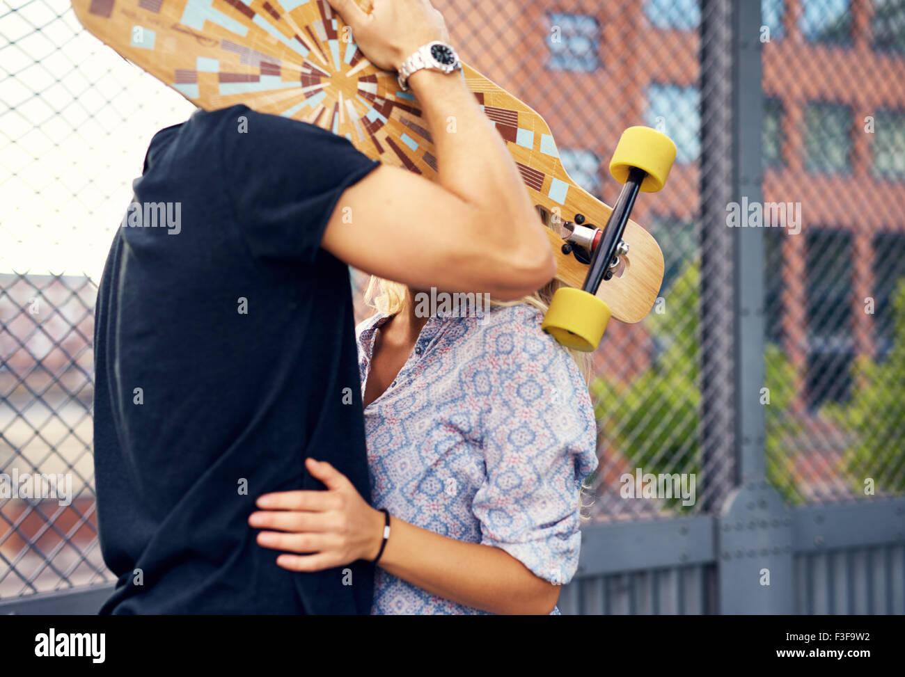 Accarezzando giovane nascondersi dietro lo skateboard e baciare Immagini Stock
