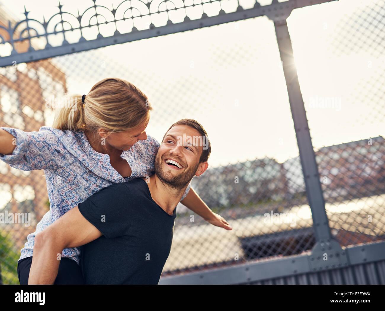 Amare giovane divertendosi, donna sulla Le Mans indietro, piggyback Immagini Stock