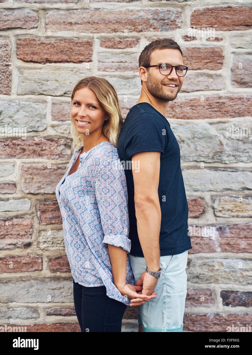 Tre quarti di colpo di una felice coppia giovane in piedi di schiena tenendo le mani e sorridente alla fotocamera Immagini Stock