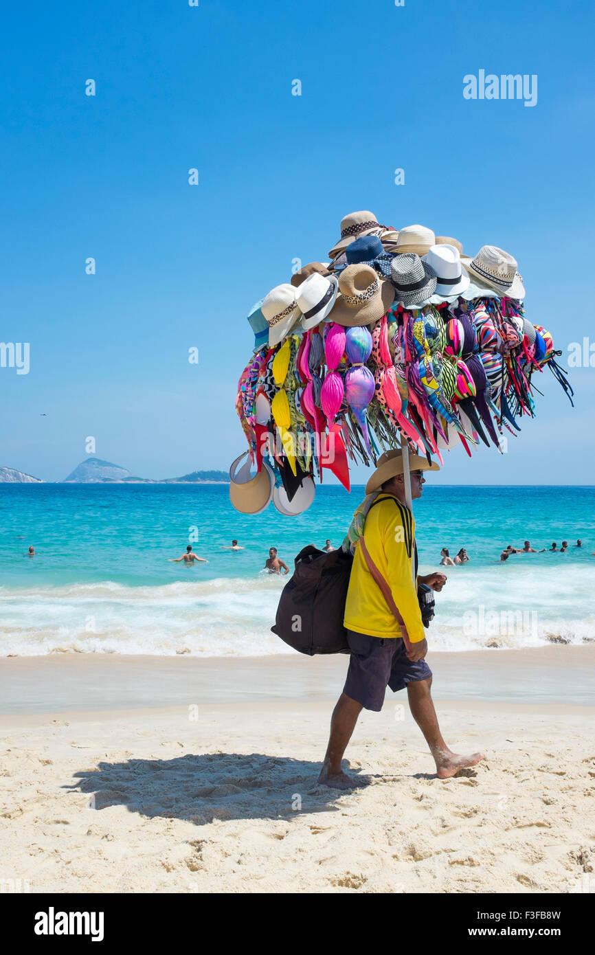 RIO DE JANEIRO, Brasile - 22 gennaio 2014: Spiaggia venditore a vendere bikini e cappelli porta la sua merce sulla Immagini Stock
