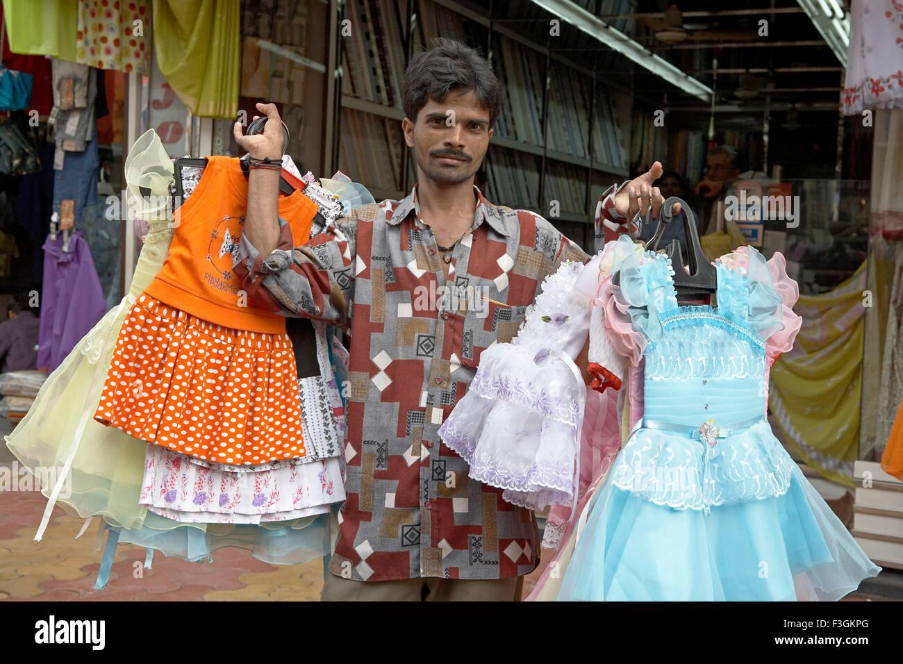 Un hawker visualizza Pronta abiti indiani come egli cammina lungo una  strada trafficata   Mumbai Bombay 21a825d6e73