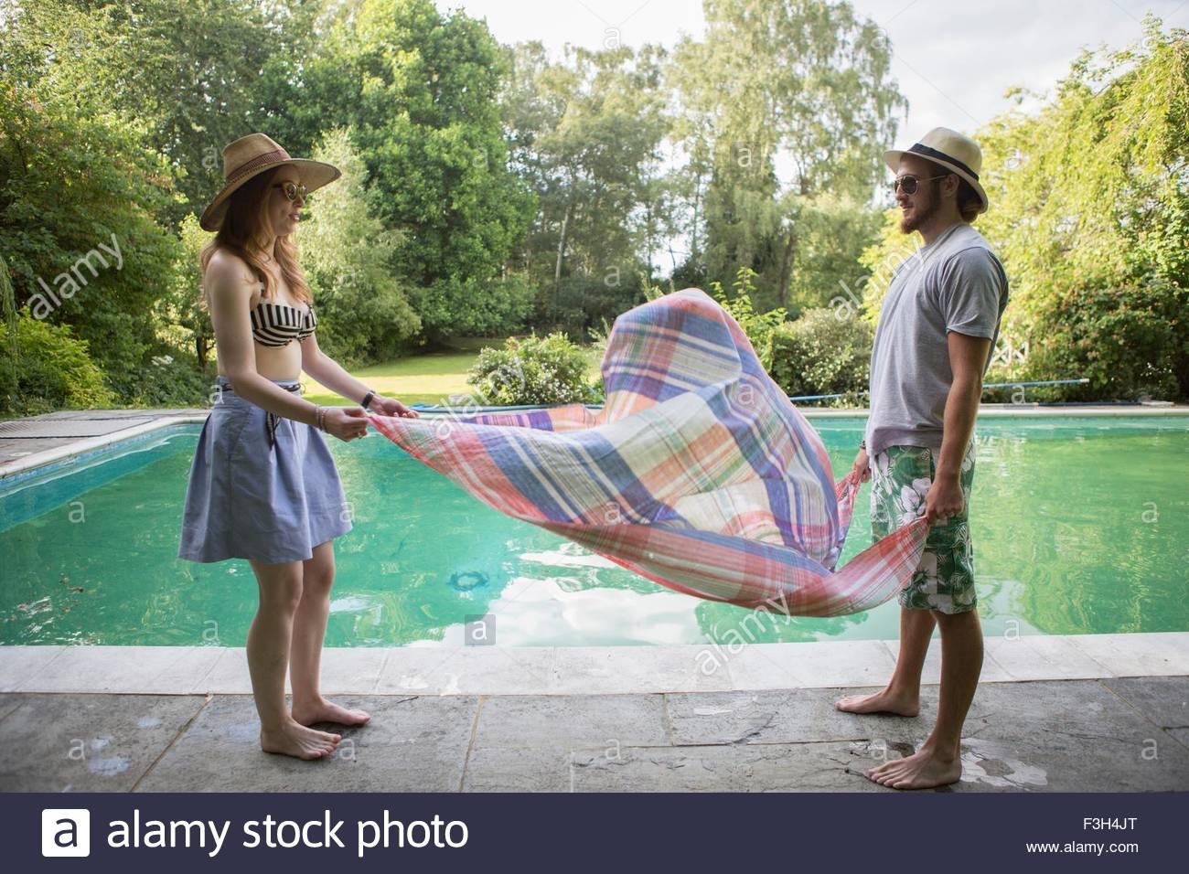 Giovane mettendo sarong giù accanto alla piscina Immagini Stock