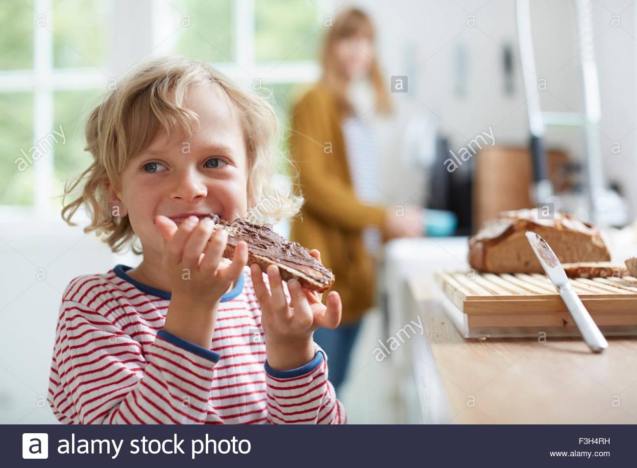 Ragazzo giovane mangiare pane con cioccolato da spalmare, madre in background Immagini Stock