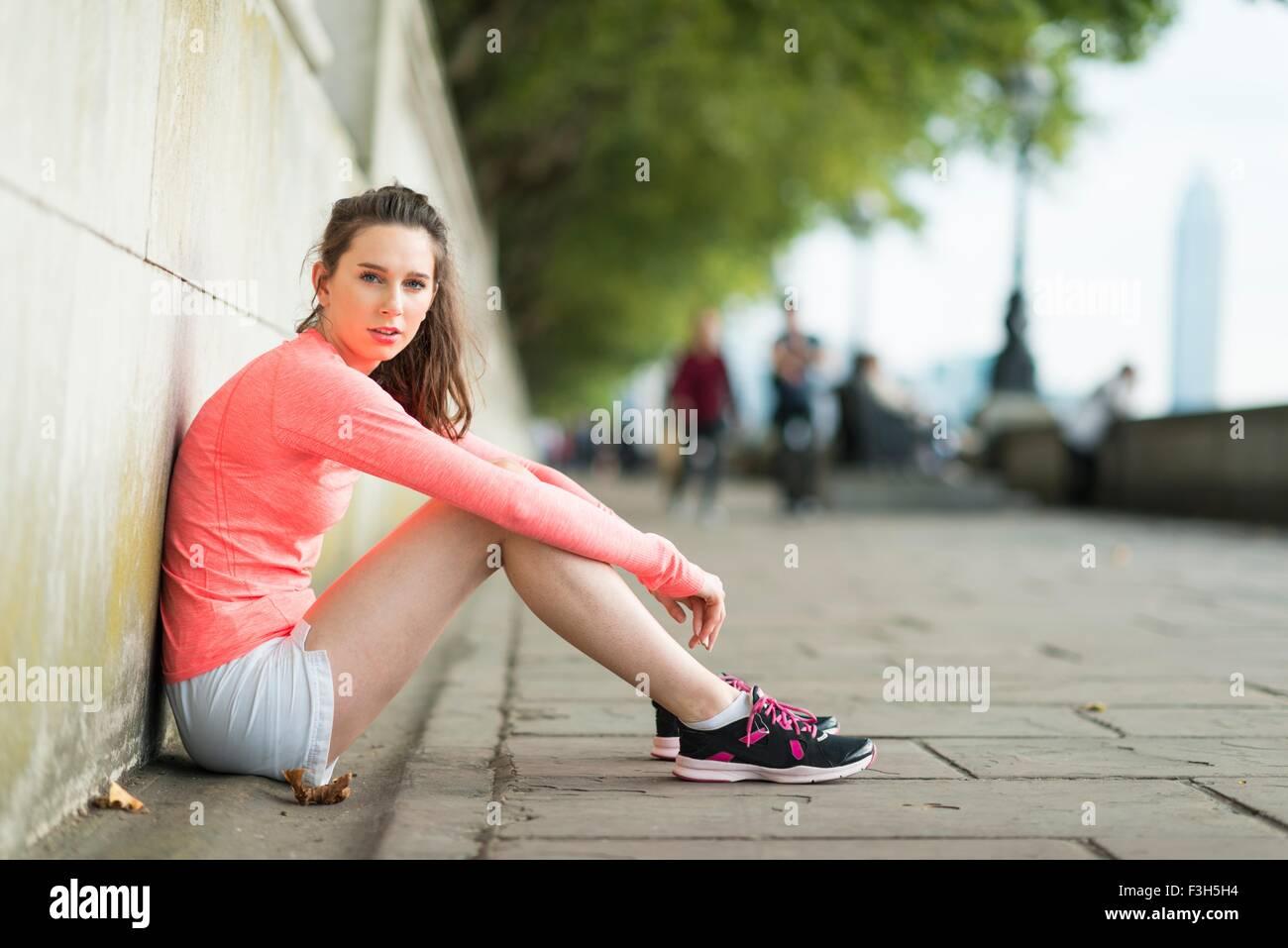 Ritratto di giovane donna seduta runner lungo il fiume Immagini Stock