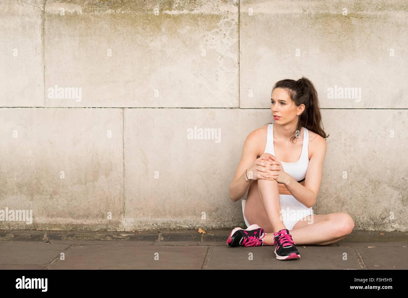 Giovani femmine runner seduta sul marciapiede guardando lateralmente Immagini Stock