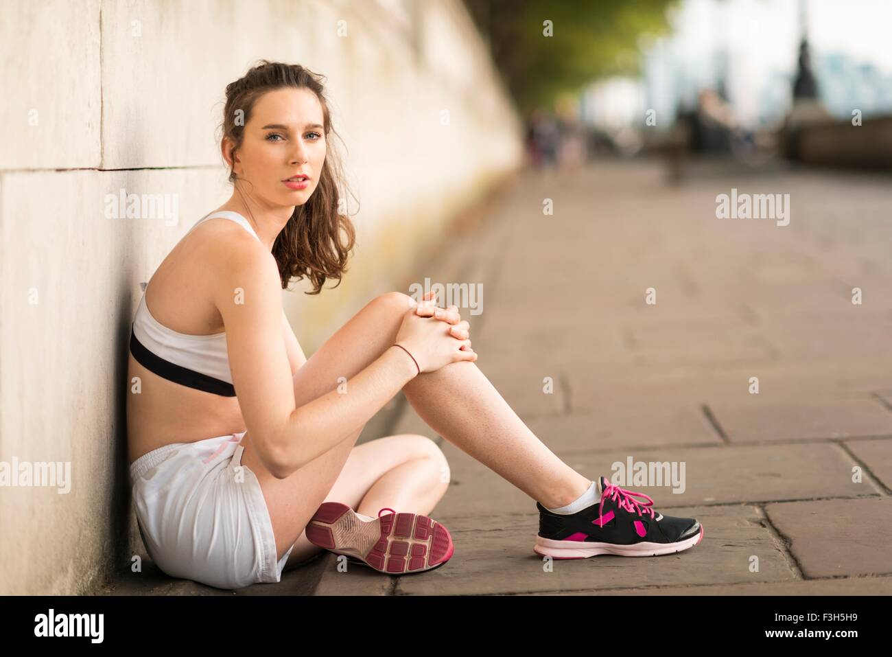 Ritratto di giovane donna seduta runner su Riverside Immagini Stock