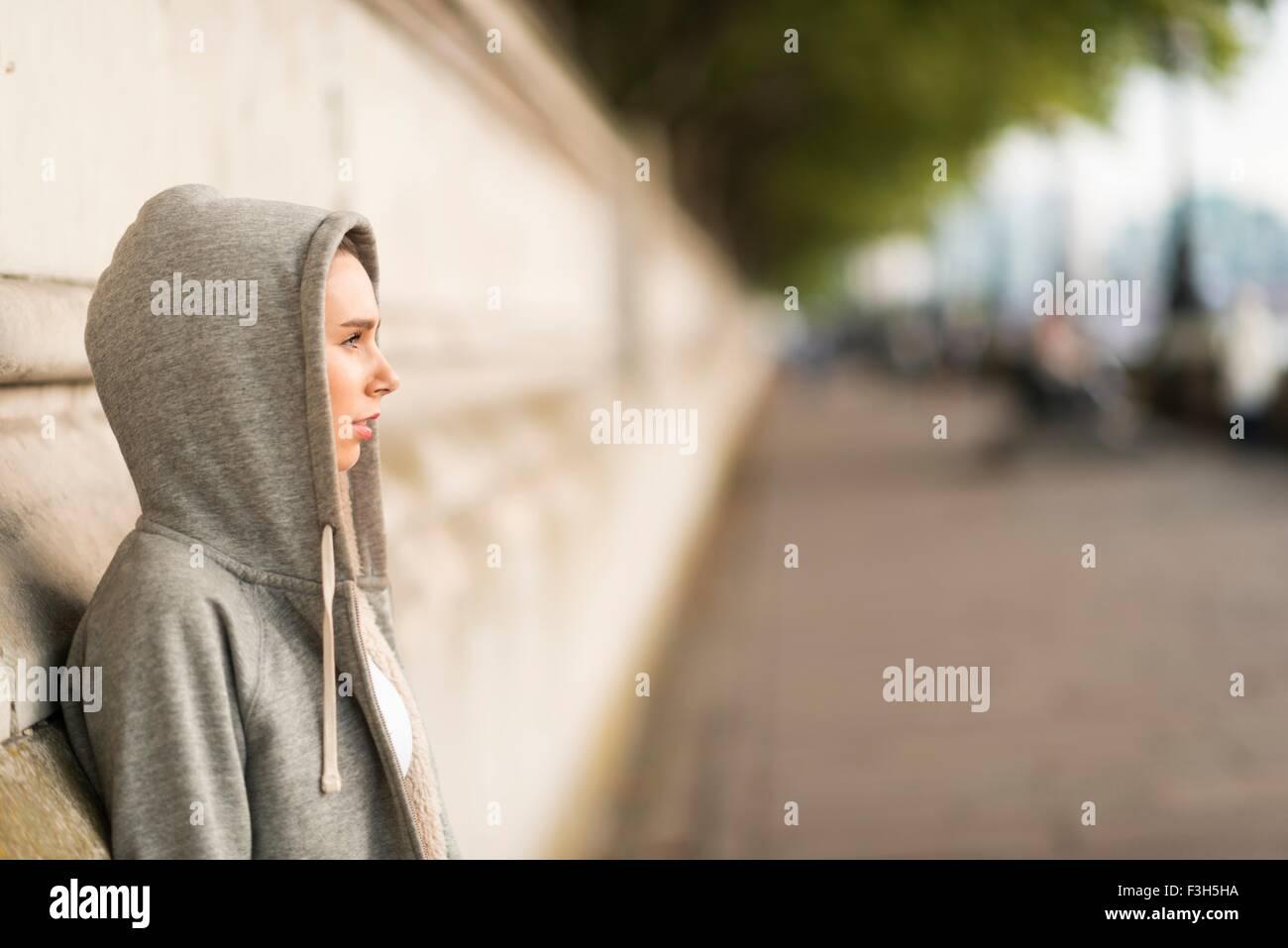 Giovane donna indossa felpa con cappuccio grigio guardando fuori dal Riverside Immagini Stock