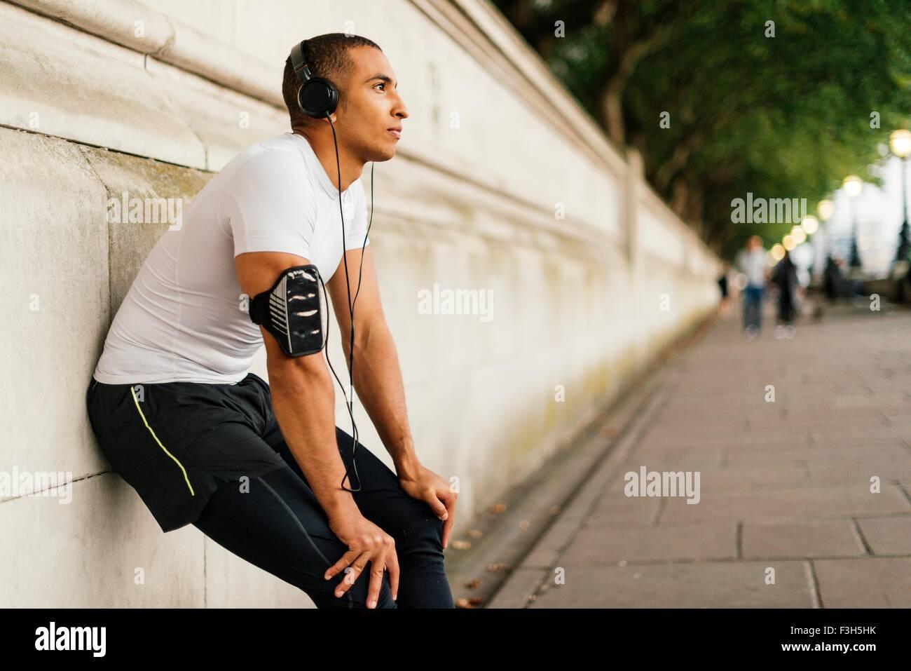 Runner maschio che indossano le cuffie prendendo una pausa su Riverside Foto Stock