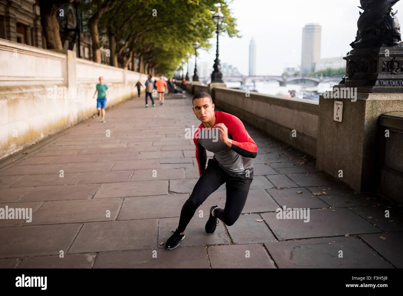 Giovane uomo allenamento di velocità lungo argine Immagini Stock