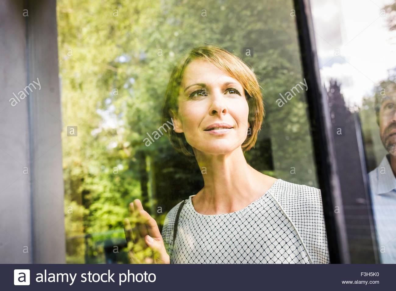 Coppia matura guardando attraverso la finestra della nuova casa Immagini Stock