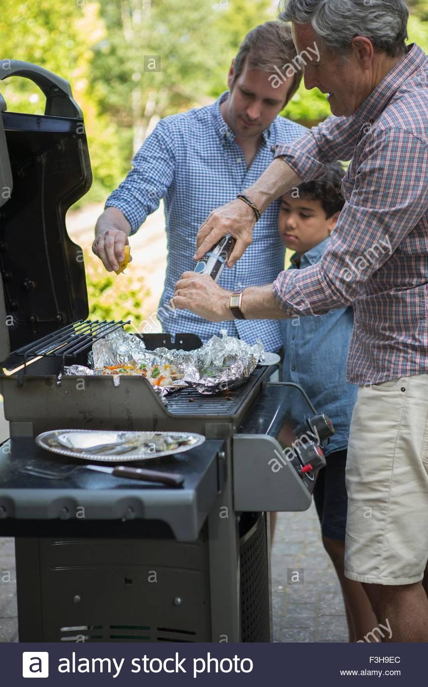 Tre generazioni la famiglia preparare del cibo su barbecue Immagini Stock