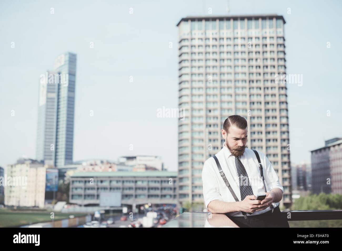 Imprenditore elegante smartphone lettura aggiornamento testo sul balcone di office Immagini Stock