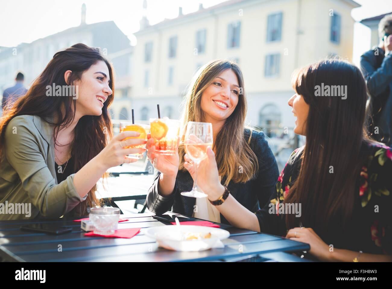 Tre giovani donne elevare un toast al cafè sul marciapiede Immagini Stock