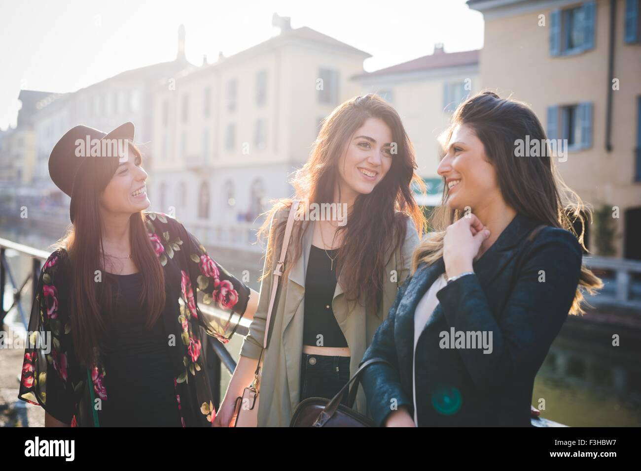 Tre giovani donne in chat sul canal waterfront Immagini Stock