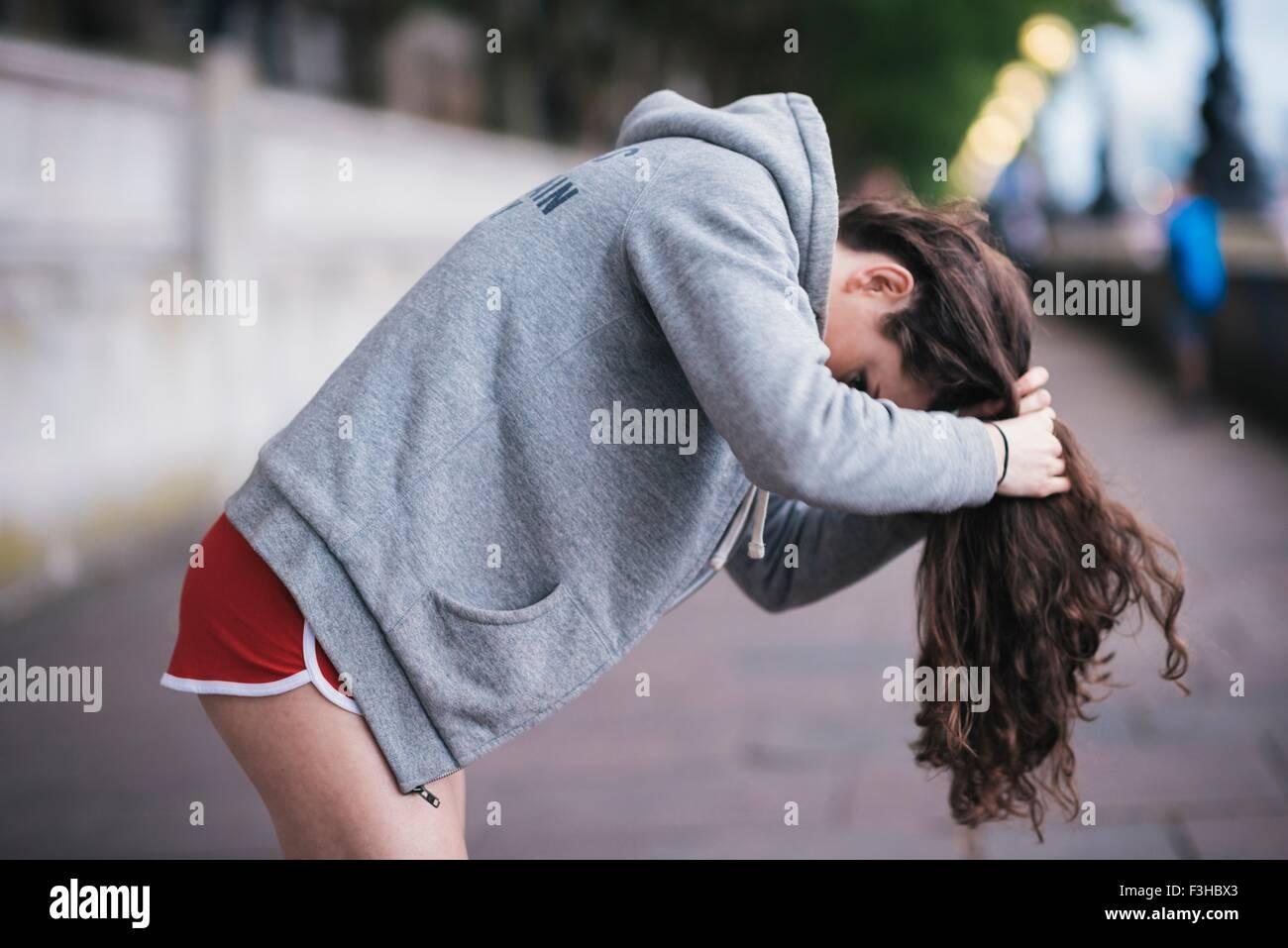 Giovane femmina legatura a runner i capelli lunghi su Riverside Immagini Stock