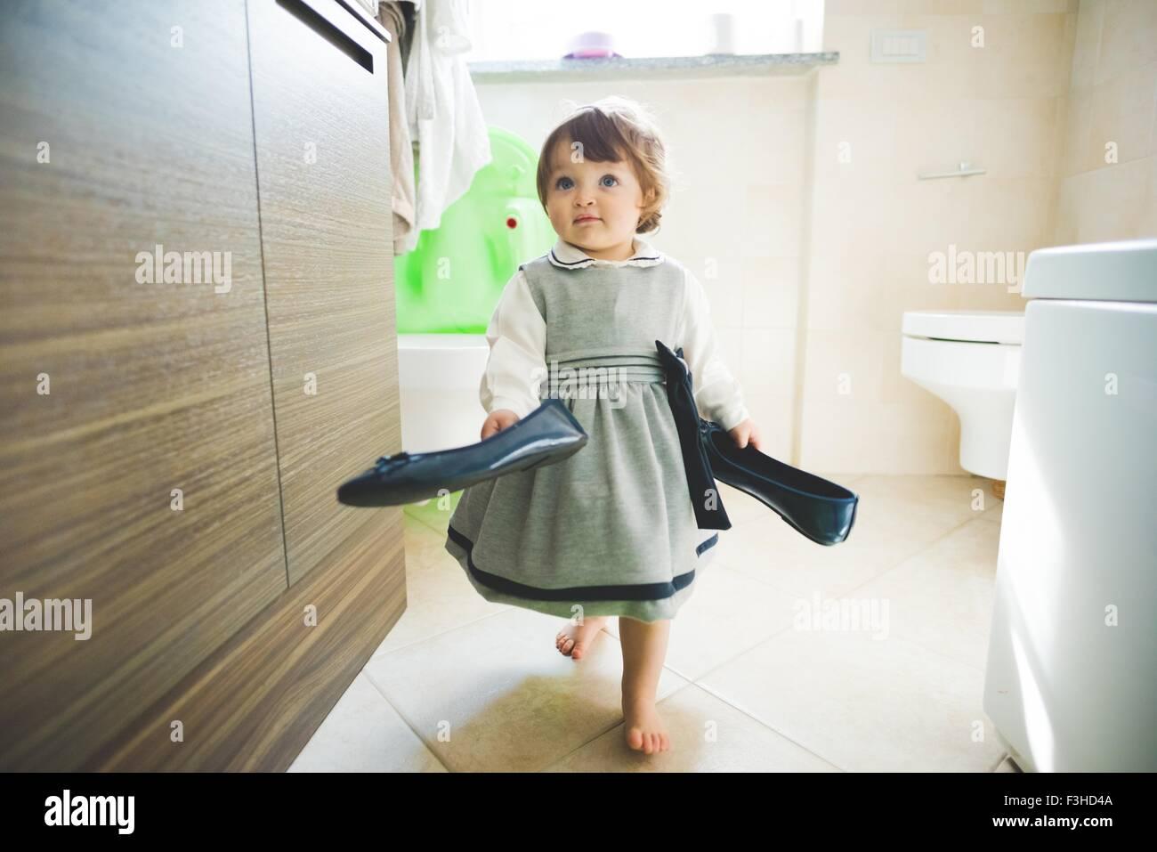 Toddler femmina porta scarpe da donna a casa Immagini Stock