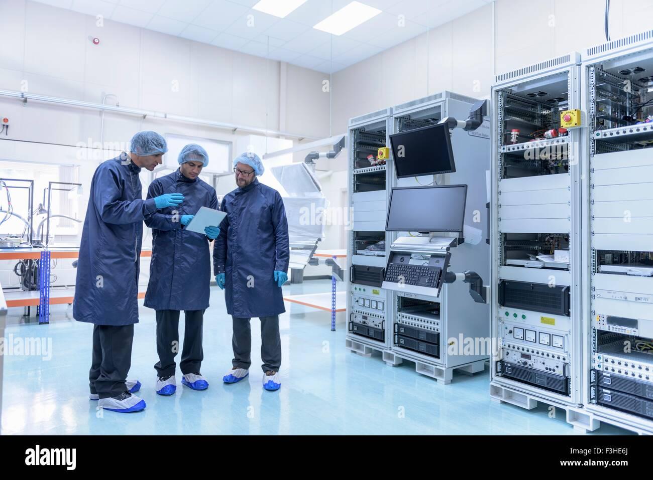 Lavoratori in camera pulita in fabbrica di componenti elettronici Immagini Stock