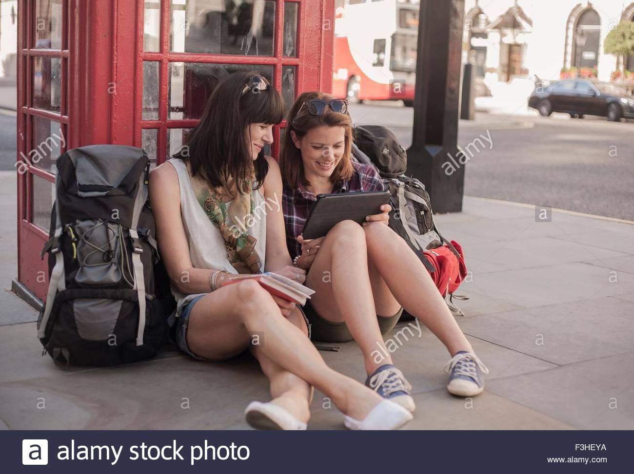 Due donne backpackers seduti sul marciapiede pianificazione percorso sulla tavoletta digitale, London, Regno Unito Immagini Stock