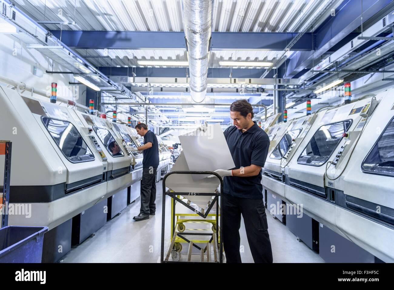 I lavoratori nella scheda di circuito manufacturing factory Immagini Stock