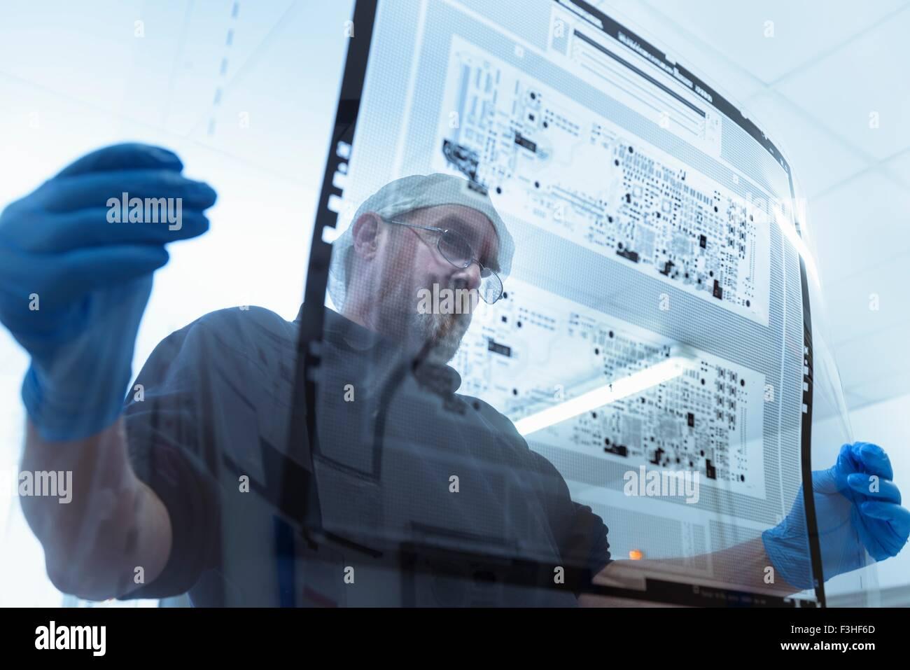 Lavoratore di ispezionare il circuito stampato foglio negativo nella scheda di circuito factory Immagini Stock