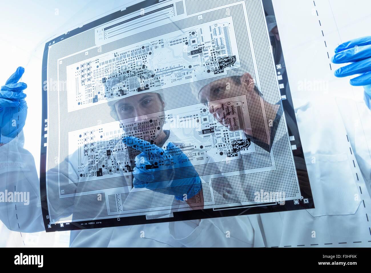 I lavoratori di ispezionare il circuito stampato foglio negativo nella scheda di circuito factory Immagini Stock