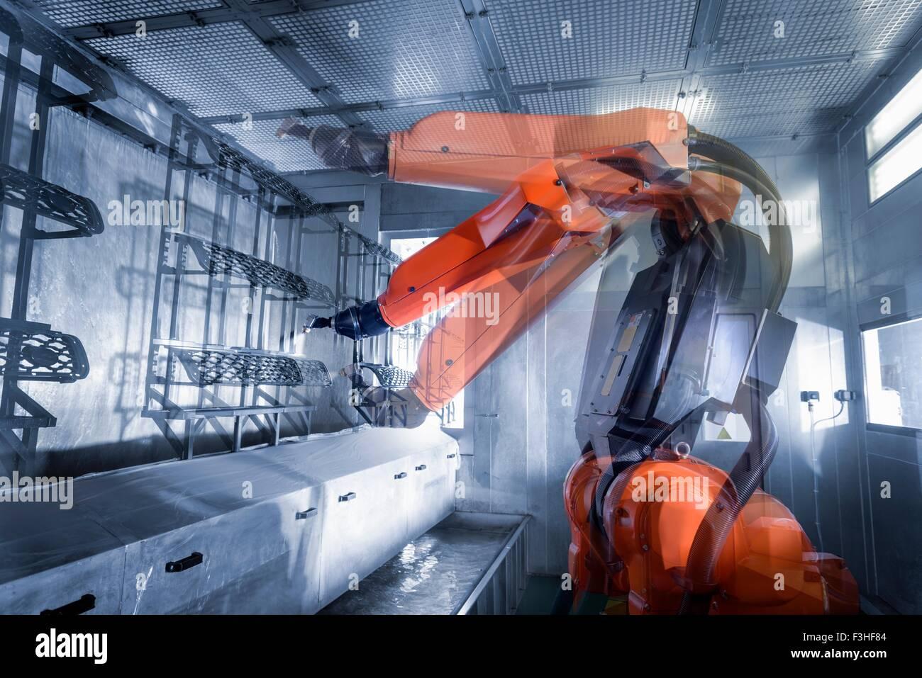 Esposizione multipla di robot di verniciatura a spruzzo di componenti automobilistici in vernice spray fabbrica, Immagini Stock