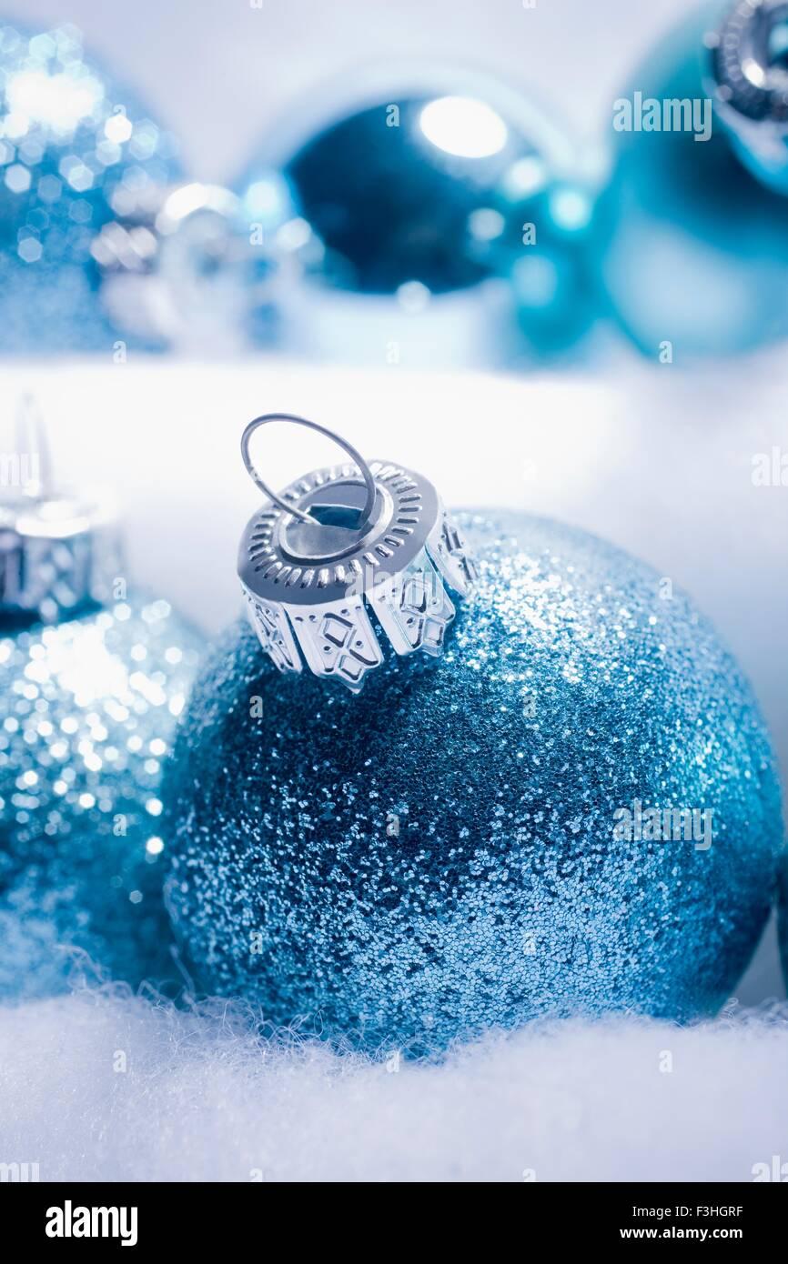 Ritagliato shot di blu scintillanti baubles di Natale nested è fake snow Immagini Stock